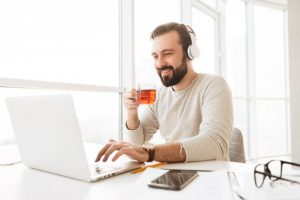 european-joyous-man-with-short-brown-hair-drinking-tea-listening-music-via-wireless-headphones-while-using-notebook_171337-27088
